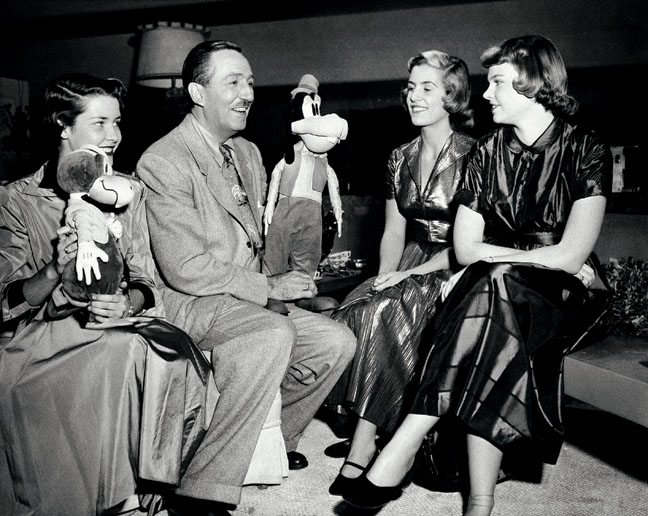 Walt Disney gives some advice to his two teenage daughters, Diane and Sharon, right, about their television debut which will take place Christmas Day, Dec. 7, 1950. Louisa Wallace, left, daughter of trhe show's director, gets in on the advice. The show will take place in Hollywood. (AP Photo)